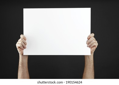 Man in black cloths holds  poster