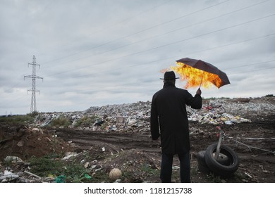 A man in a black coat and hat with a burning umbrella in his hand on the background of a garbage dump