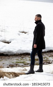 Man in a black coat standing by the snowy river