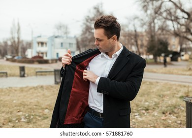 the man in a black coat and a suit walks down the street. He looks for something in an inside pocket of a jacket. He has very solid look.