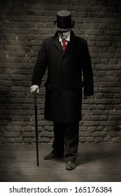 Man in the black coat, top hat and in a red tie on a wall background