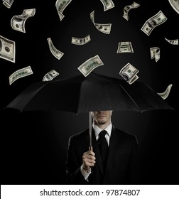 man in black costume with blak umbrella under rain of  currency note,  concept economics  crisis