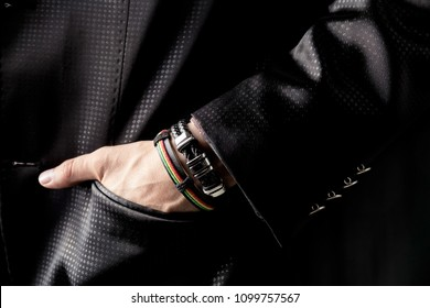 Man in black costume and with colorful bracelets on hand. Closeup of man with jewelry on hand.