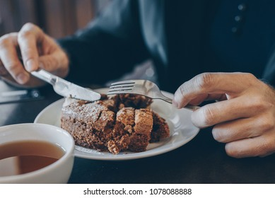 Man in black eating cake in cafe, closeup, selective focus