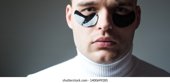 Man with black eye patches close up face. Beauty treatment. Skin care. Metrosexual concept. Focused treatments for under eye area. Minimizes puffiness and reduce dark circles. Eye patches for men.