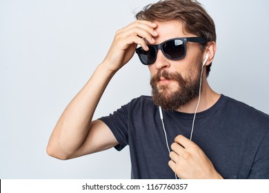 a man in black glasses and headphones is holding his hand near his forehead