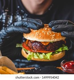 Man in black gloves eating beef burger. Closeup