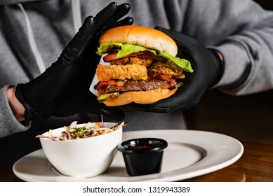 man in black gloves eating burger in the restaurant