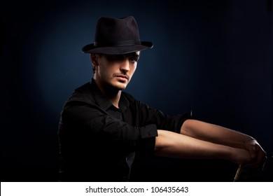 man in a black hat on black background