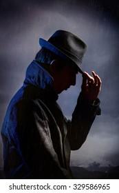 Man in black hat in the rain at dark overcast sky