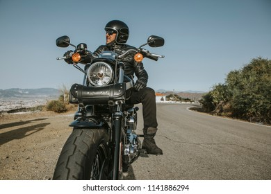 Man with black helmet, jacket and sunglasses standing on a classic American motorcycle.