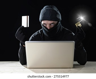 man in black holding credit card and lock using computer laptop for criminal activity hacking bank account password and private information cracking password for illegal access in cyber crime concept