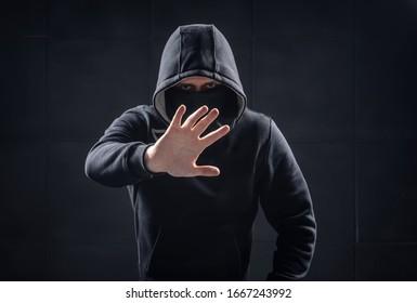 Man in black hoodie make stop sign by hand.