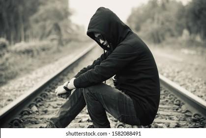 Man in a black hoody dress sitting on a railway tracks unique photo