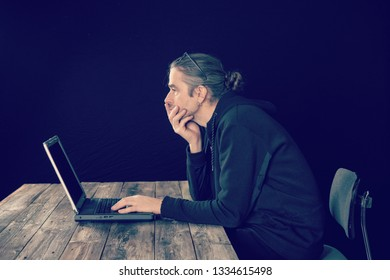 man in black hoody with laptop  in front of black background looking thoughtful