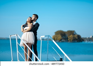 Man in black hugs tender lady in short white dress while they stand over the lake