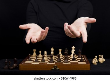 man  in a black jacket points out with her hands on the opponent in the game of chess, lifting her hands on the chessboard