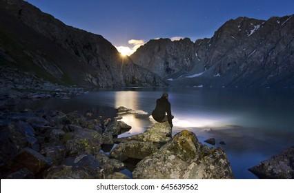 man in black jacket sitting near blue lake in mountains at night