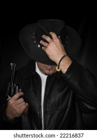 Man in black leather coat and hat holding a western-style revolver