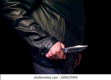 A man in a black leather jacket with a knife in his hand, no face