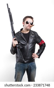 Man in black leather jacket and sunglasses with shotgun