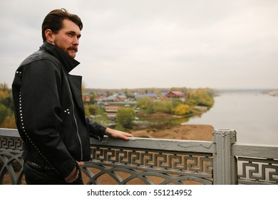 Man in black leather jackets looking at river.