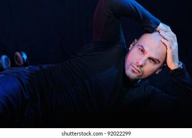 Man in black lying on the floor. Studio-style portrait