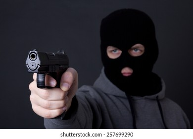 man in black mask aiming with gun over grey background