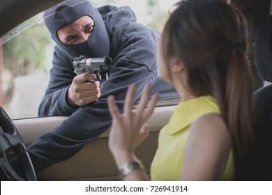 Man in the black mask pointing a gun to scare young lady in the car and try to rob a car.