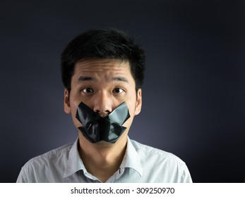 Man with black masking tape over his mouth on black background