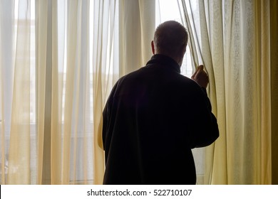A man in black moves the curtain aside to look out trough the window