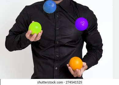 Man in black shirt juggling with multicolored oranges