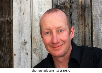 Man in a black shirt with a natural wooden background.