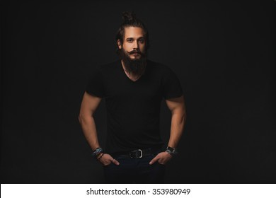 man in a black shirt and pants with a beard and mustache posing in the studio on a black background, the macho male muscular guy,handsome man portrait of a brutal male movie star fashionable clothes