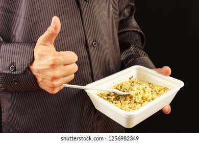 Man in black shirt recommends and likes instant noodles on a black background