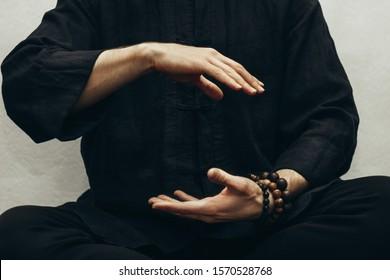 A man in black shirt sitting and doing qigong. Hands direct energy. Prayer, gratitude.Practicing monk. Qi energy. Yoga pose. Healing retreats. Close up.