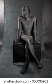 man in black skin-tight body suit and his face covered by suit . He is sitting on a black bench. Legs crossed