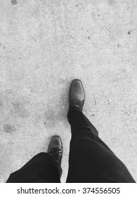 Man in black slack and black shoes stepping his right foot forward on concrete floor. Walking to his future and success in business