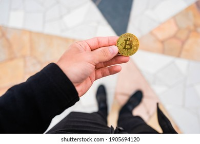 Man in black stands and looks at the bitcoin in his hand. Bitcoin in hand. Man hold bitcoin in his hand with lines in the background that converge into a coin.