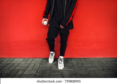Man in black stands near a red wall. Look. Hype sneaker background. 	 sneakers