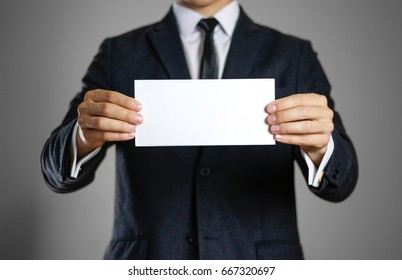 A man in black suit holding blank clear white of the sheet. Closeup. Isolated.