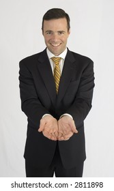Man in black suit holding hands smiling at camera