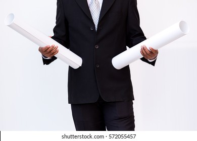 Man in black suit holding some blue print on white background.