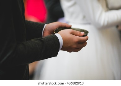 Man in black suit holds a steel plate in his hands