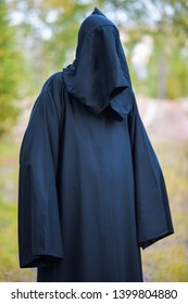 A man in a black suit with a hood stands in the woods on a green background. Vertical photography