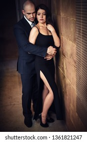 A man in a black suit hugs from behind a beautiful dark-haired girl in a black dress with a slit at the waist. Vertical photography