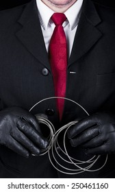 Man in black suit and leather gloves holding metal string, close up