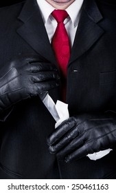 Man in black suit and leather gloves cleaning knife, close up