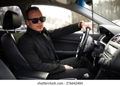 man in a black suit sitting behind the wheel