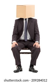 Man in black suit sitting on a wooden chair with a cardboard box on his head isolated on white background